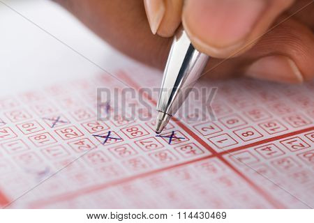 Person Marking Number On Lottery Ticket With Pen