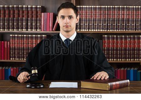 Portrait Of Confident Judge Hitting Mallet At Desk