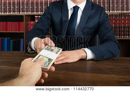 Lawyer Taking Bribe From Client At Desk