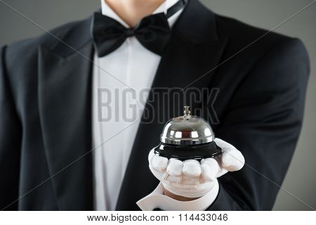 Midsection Of Waiter Holding Service Bell