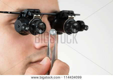 Jeweler Examining Diamond With Magnifying Loupe