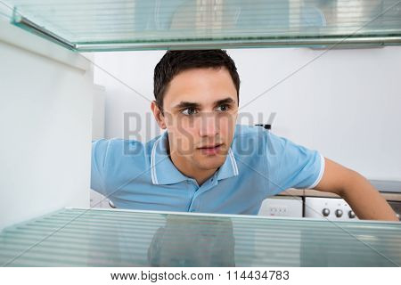 Shocked Man Looking Into Empty Refrigerator