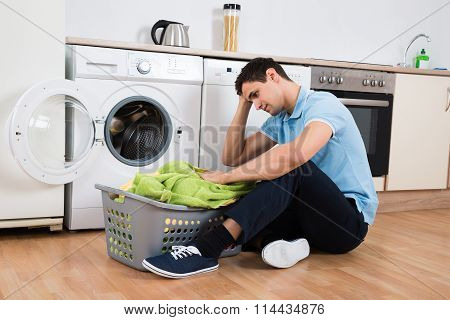 Tensed Man Looking At Laundry Basket By Washing Machine