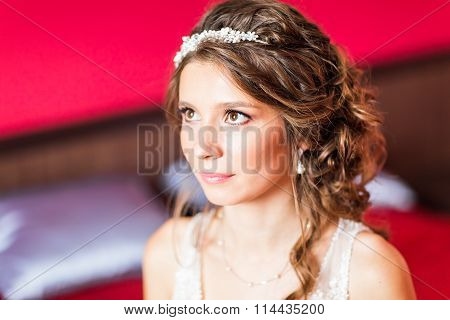 Beautiful young bride with wedding makeup and hairstyle in bedroom