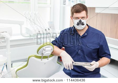 Handsome dental doctor is working with modern equipment