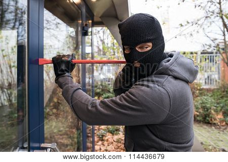 Man Using Crowbar To Open Glass Door