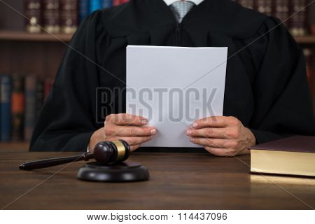 Judge Reading Document At Desk In Courtroom
