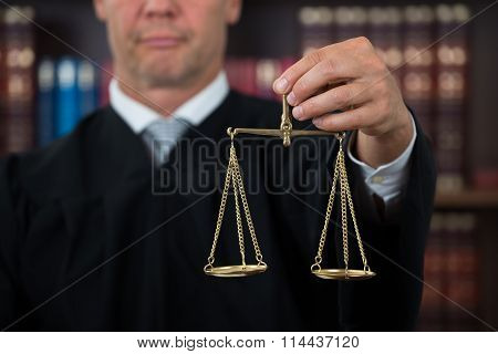 Judge Holding Law Scales In Courtroom
