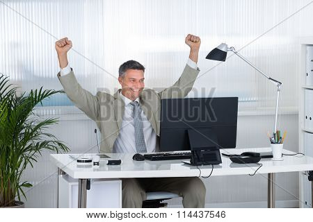 Businessman Celebrating Victory At Computer Desk