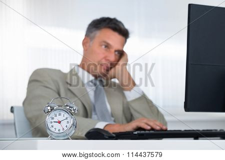 Businessman Using Computer At Desk With Focus On Clock