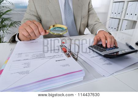 Accountant Holding Magnifying Glass To Analyze Bills