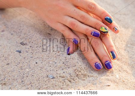 Beautiful hands with a professional manicure on the sand.