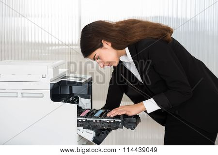 Businessman Fixing Cartridge In Photocopy Machine At Office