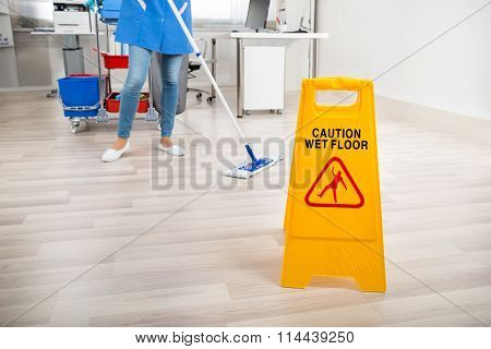 Janitor Mopping Floor By Wet Caution Sign In Office