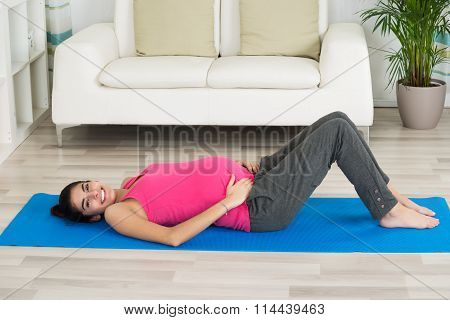 Portrait Of Happy Pregnant Woman Lying On Exercise Mat
