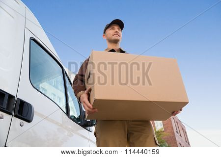 Delivery Man Carrying Cardboard Box By Truck Against Sky