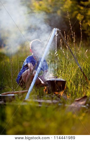 Little Boy Cooks On A Fire In Wood
