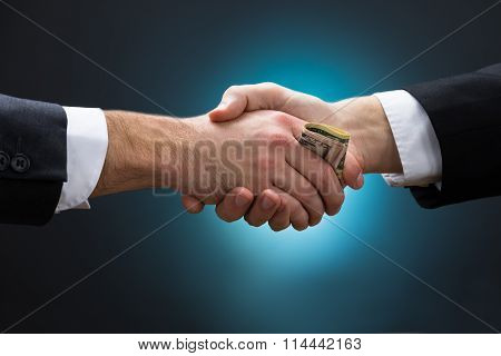 Businessman Shaking Hands While Giving Bribe To Partner