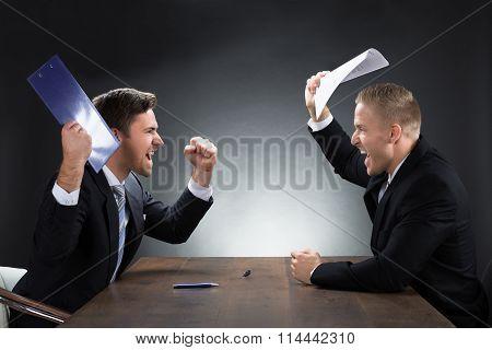 Aggressive Young Businessmen Arguing At Desk