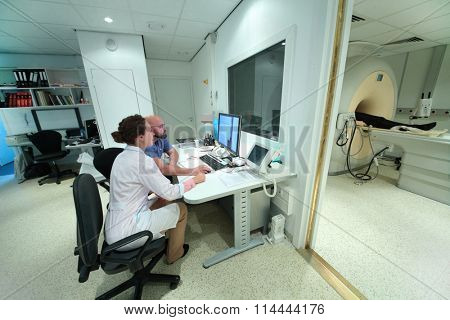 RUSSIA, MOSCOW - AUG 31, 2015: two experienced physicians in control room, and magnetic resonance imaging machine with patient