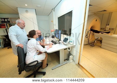 RUSSIA, MOSCOW - AUG 31, 2015: three experienced physicians in control room, and magnetic resonance imaging machine with patient in multidisciplinary Clinic Center Endosurgery and Lithotripsy (CELT)