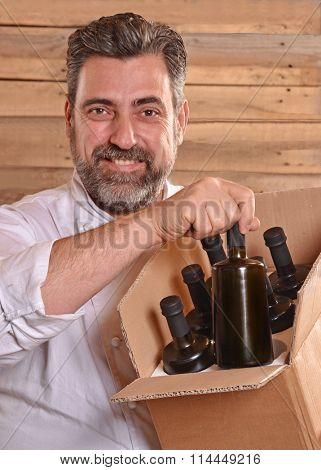 Chef holding extra virgin olive oil bottles box.