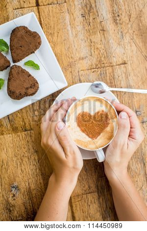 Woman Holding Hot Cup Of Coffee, With Heart Shape And Chocolate Cake In The Shape Of Heart