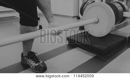 A man performs an exercise with a barbell