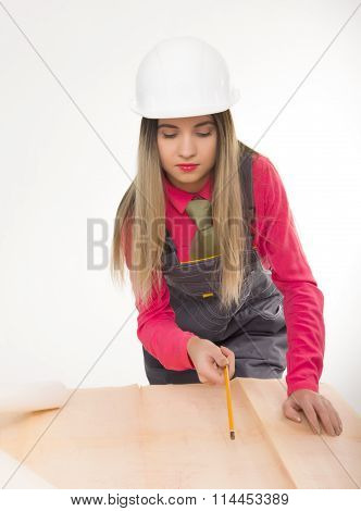 Female civil engineer standing next to the table, she bent over blueprints