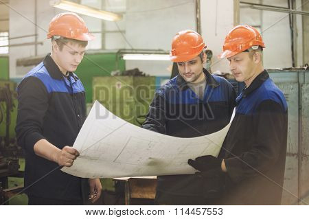 Men With Drawings Working In An Old Factory To Install The Equipment In Helmets