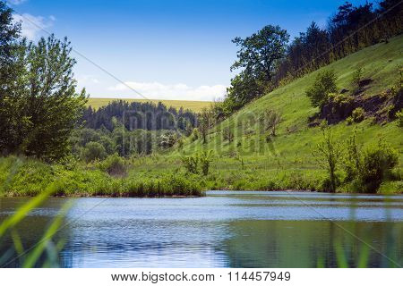 Landscape Of A River, Green Grassy Hills With Trees