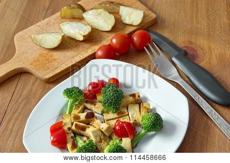 pieces of roasted tofu with broccoli, tomatoes and soy sauce