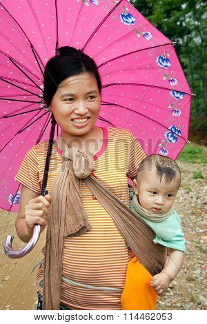 Vietnamese mother and daughter with a pink umbrella