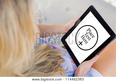 Woman sitting on beach in deck chair using tablet pc against place text here
