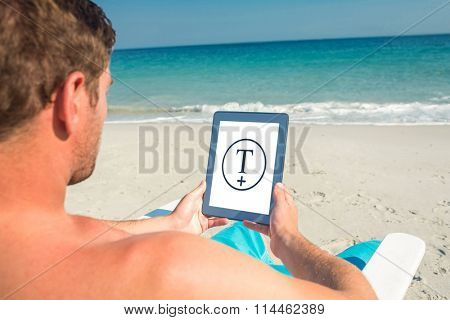 Man using digital tablet on deck chair at the beach against t plus circle