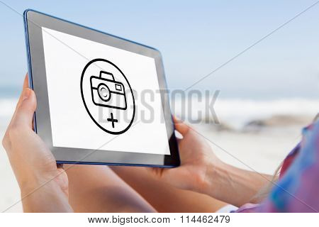 Woman sitting on beach in deck chair using tablet pc against photography apps
