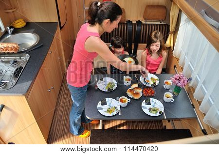 Family eating together in RV interior, travel in motorhome (camper, caravan) on vacation