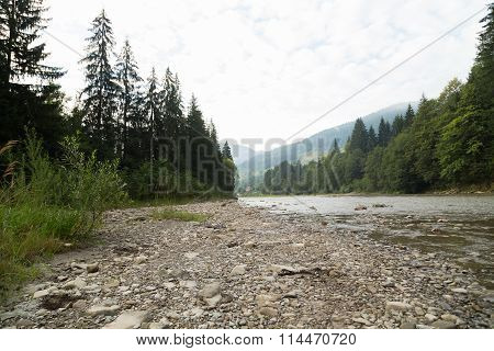 Beautiful rocky mountain landscape. Stones and boulders strewn shore of a mountain river
