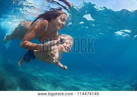 Mother With Child Swim Underwater In Blue Beach Pool