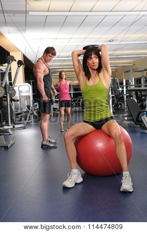 Mature woman in foreground with man and young woman in background exercising in gymnasium