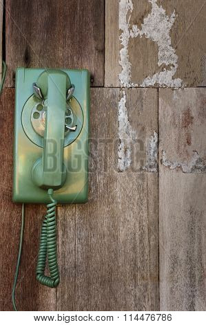 Old Phone In Green Color Hanging On Wooden Wall