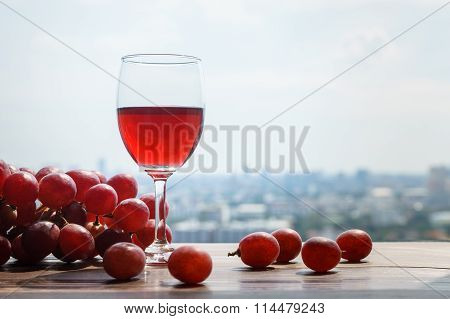 Glass Of Red Grapes Wine On The Table