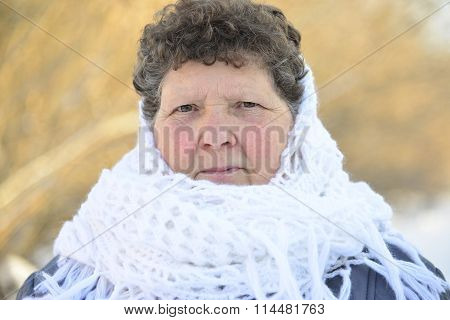 elderly woman in  white knitted shawl on her head