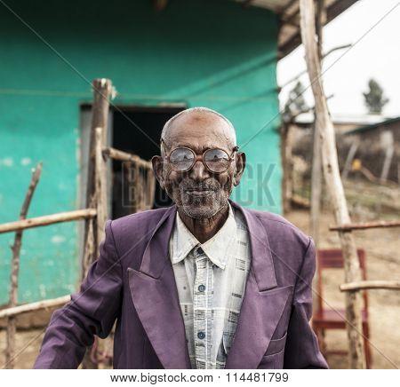 OROMIA, ETHIOPIA-APRIL 22, 2015: Portrait of unidentified Ethiopian man with thick glasses outside his home in Oromia