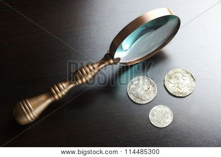Vintage Magnifying Glass And Old Silver Coins On Black Table