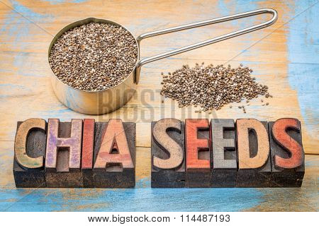 chia seeds in a metal measuring scoop and a text in vintage letterpress printing blocks against grunge painted  wood