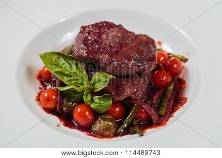 Baked meat with cherry tomatoes and basil sauce.