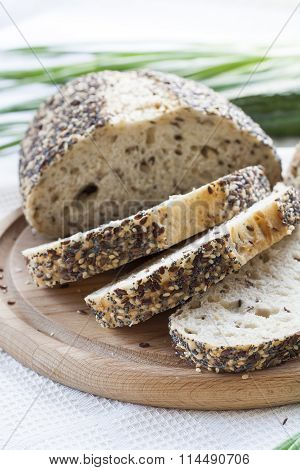 Sliced homemade bread loaf with sesame and other grains on a round desk at wooden table