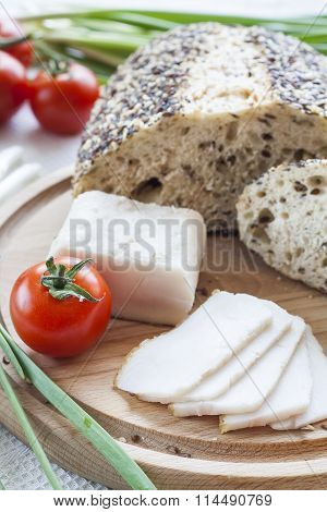 Sliced lard on a wooden desk with bread and vegetables tomatoes, cucumber and green fresh onion