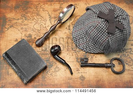 Overhead View Of  Deerstalker Hat And Private Detective Tools On The Old World Map Background. Items Include Vintage Magnifying Glass Retro Key Hand Book Or Notepad Smoking Pipe